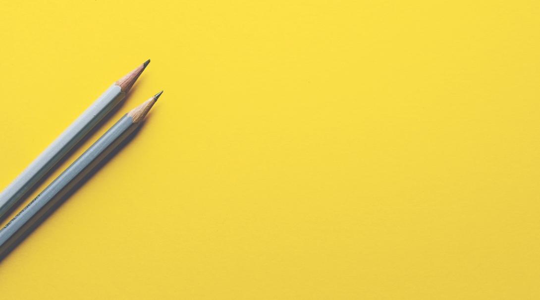 黄色の背景の左側に置かれた2本の鉛筆